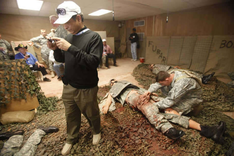 Jeet Kar, of Aker Solutions, photographs a mock situation of injured soldiers as medics get ready for their iteration while employers watch. Photo: Mayra Beltran, Chronicle
