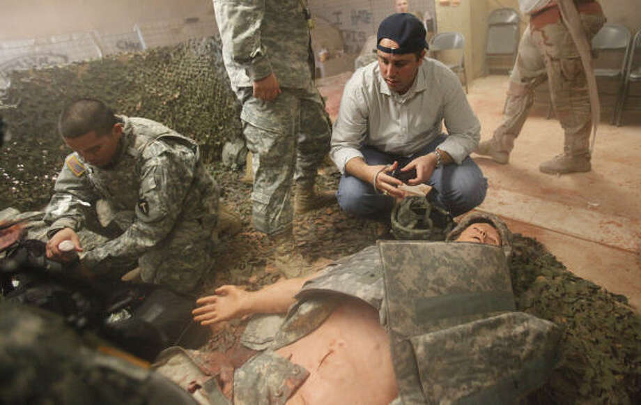 Dustin Dickschat, of GexPro Services, gets a closer look at a mock situation of injured soldiers. Photo: Mayra Beltran, Chronicle
