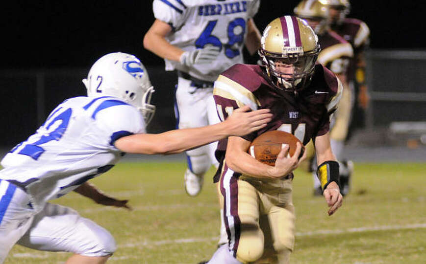Magnolia West's Dustin Corkan tries to avoid the tackles from a Shepherd defender.