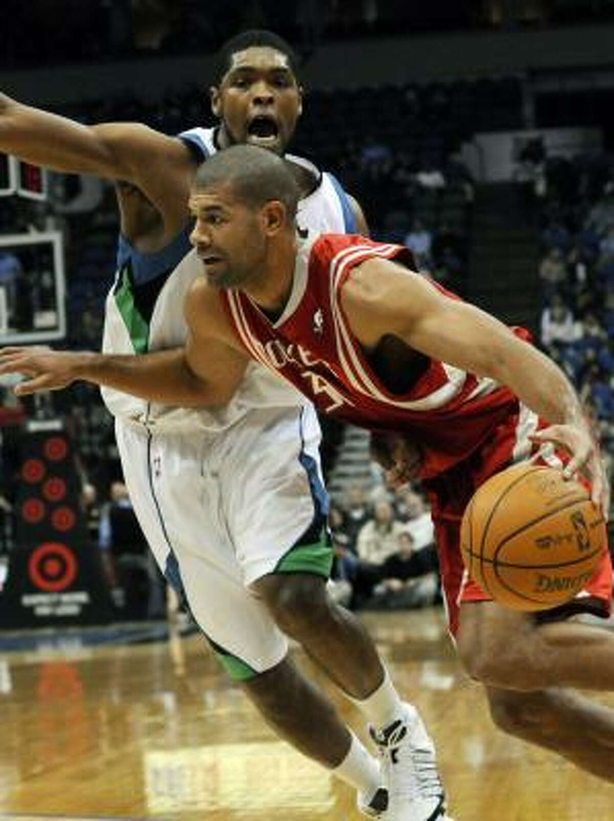 The Timberwolves' Ryan Gomes defends as Rockets forward Shane Battier drives in the first quarter.