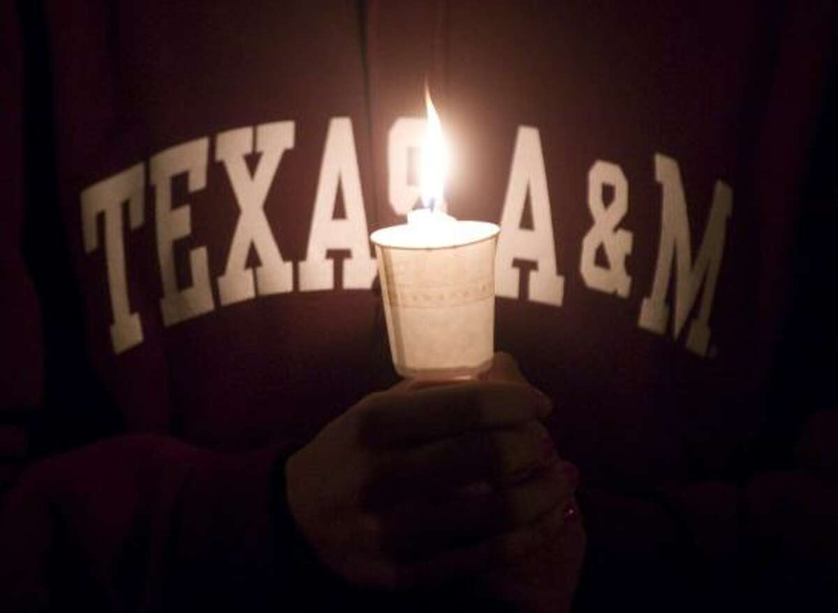 A Texas A&M student cradles a candle during a candlelight memorial service.