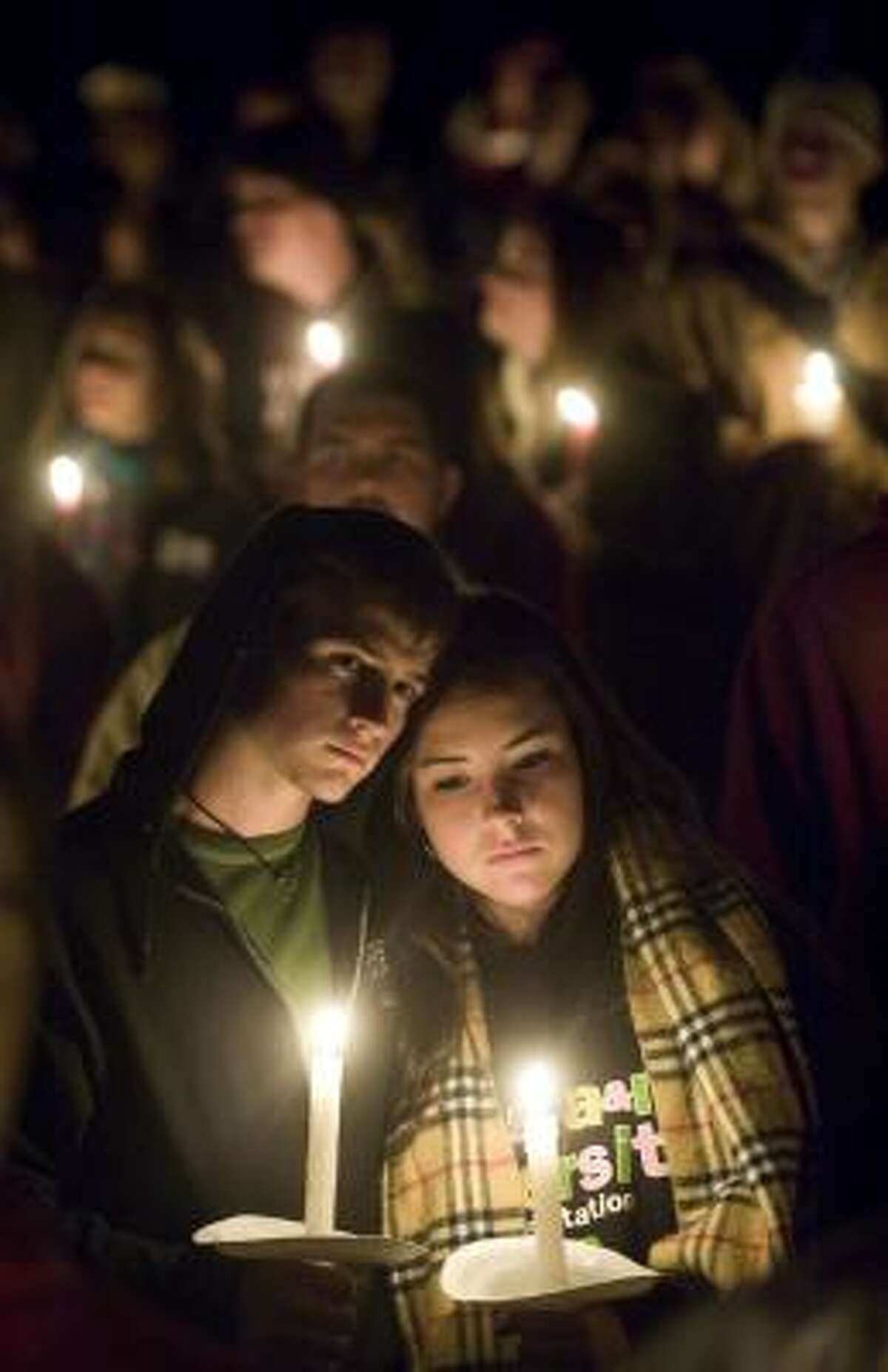 Texas A&M students Tyler Stevenson and Alexandra Brown huddle together during a candlelight memorial service in observance of the 10th anniversary of the 1999 Bonfire collapse.