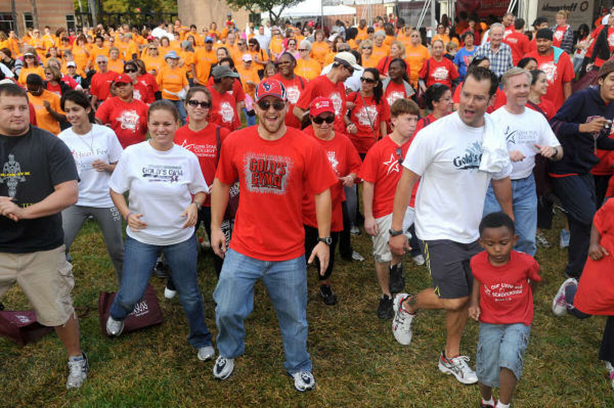Danny Klaus, center, and Tony Mazurkewicz, right, of Gold's Gym Kingwood, join Kelvin Robinson, 5, right front, of Spring, during the warm-up prior to the start of the Greater Lake Houston Heart Walk at Lone Star College-Kingwood.