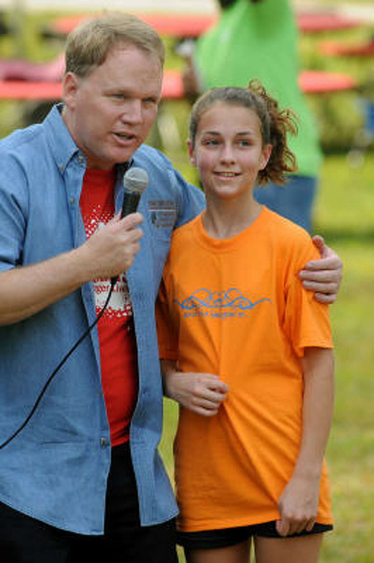 Sparky Nolan, left, Kingwood Chamber of Commerce president, visits with Shelby Corley, 12, a seventh-grader at Dayton Junior High, after she was the first-place finisher at the Greater Lake Houston Heart Walk.