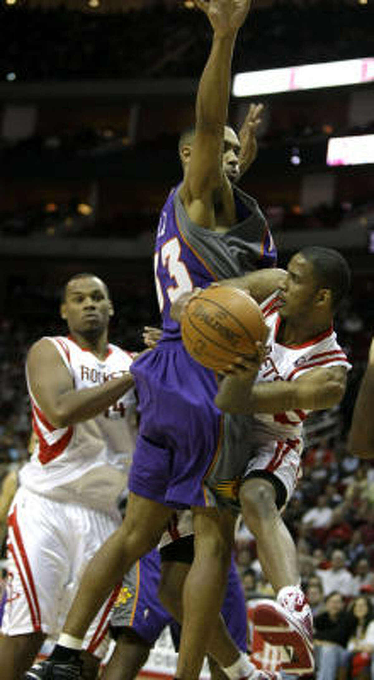 Rockets forward Trevor Ariza, right, pass the ball around Suns forward Grant Hill (33) during the fourth quarter.