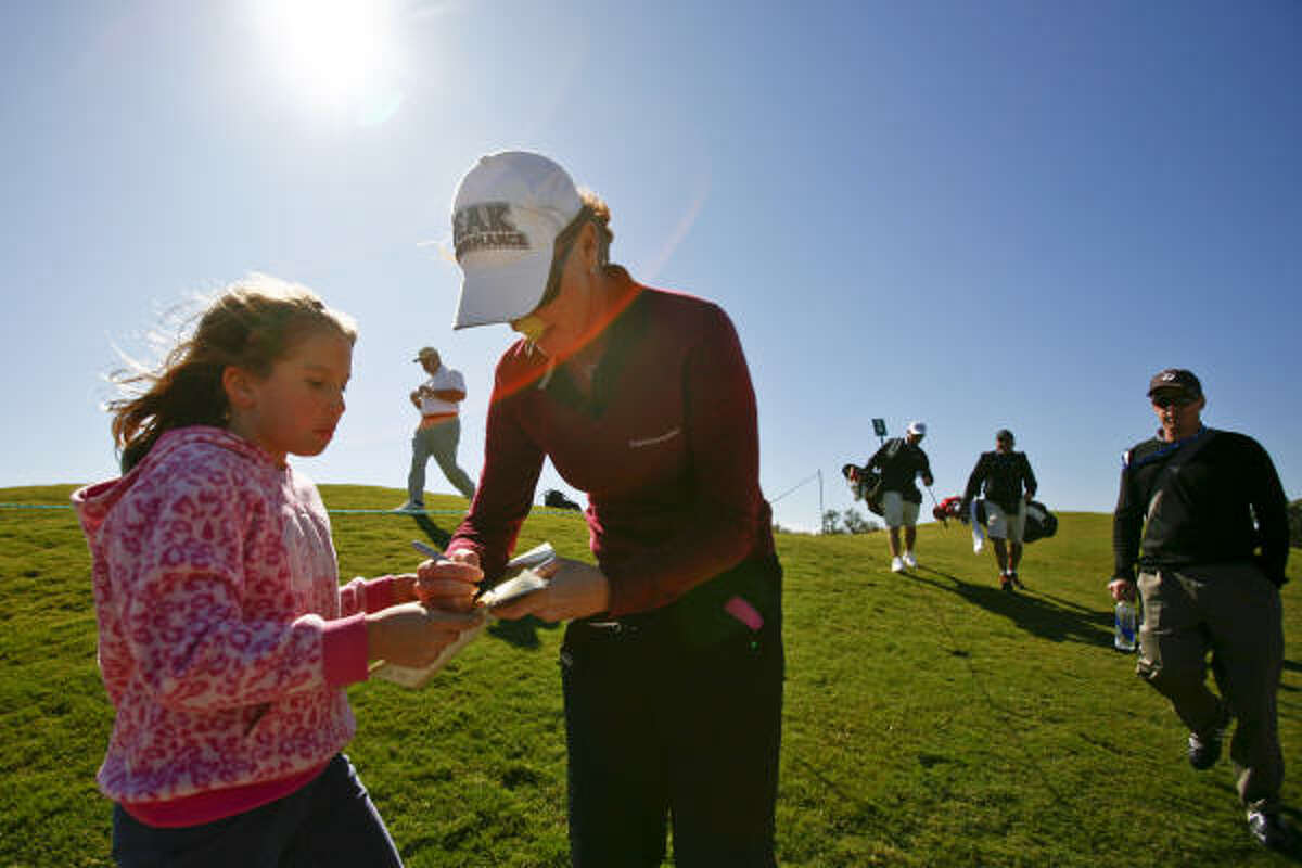 Sophie Raymond, 9, gets an autograph from LPGA golfer Helen Alfredsson during the opening day practice round.