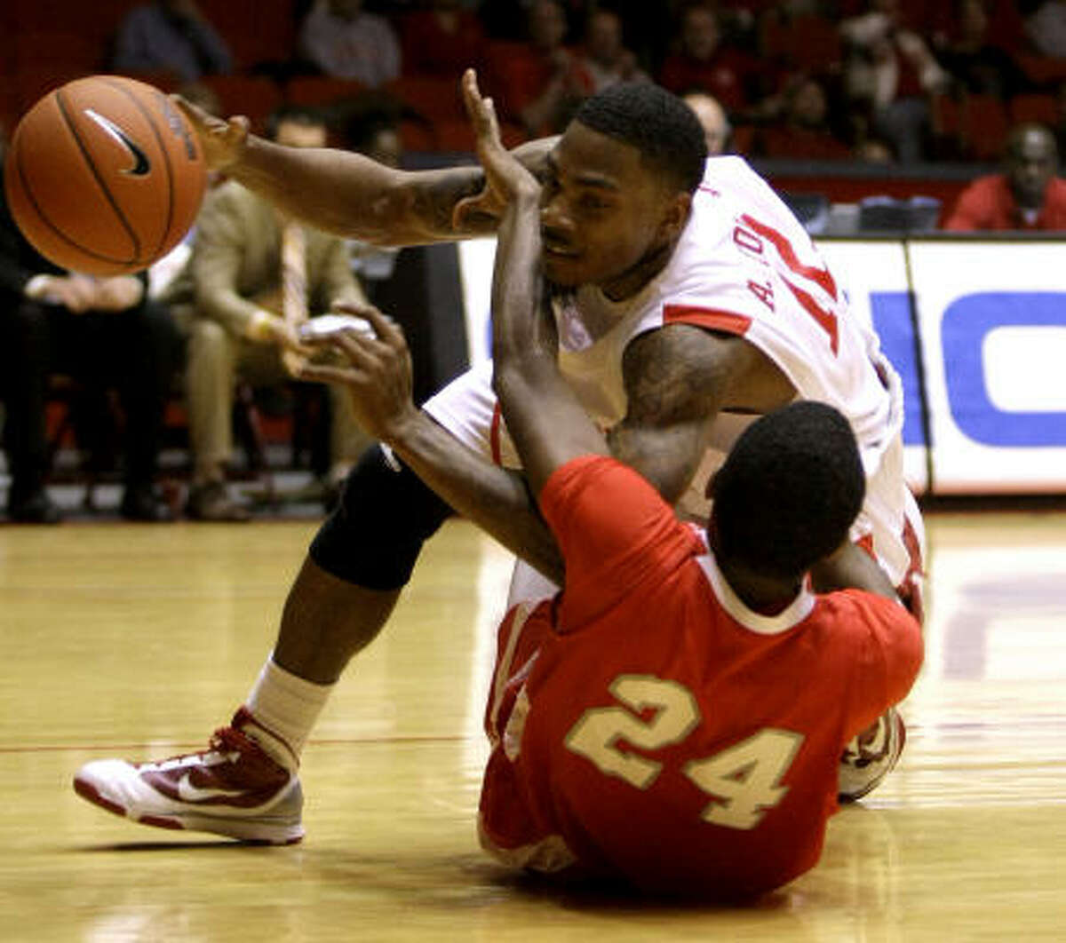 UH guard Aubrey Coleman, top, is tripped up by Nicholls State forward Kellan Carter on his way to the basket during the first half.