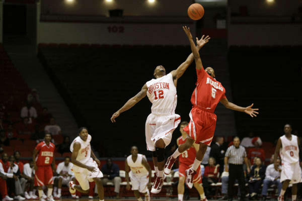 UH guard Aubrey Coleman (12) and Nicholls State guard Kenny Franklin (5) leap for a loose ball during the first half.
