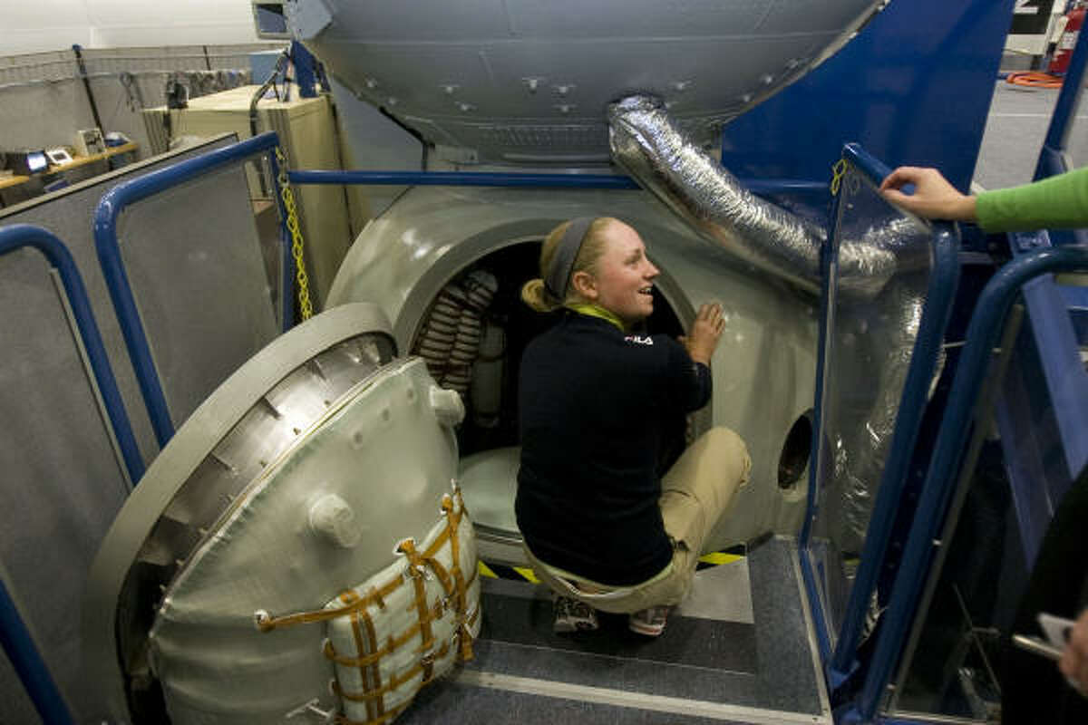 LPGA golfer Stacy Lewis gets a closer look at a model of a Russian Soyuz crew compartment.