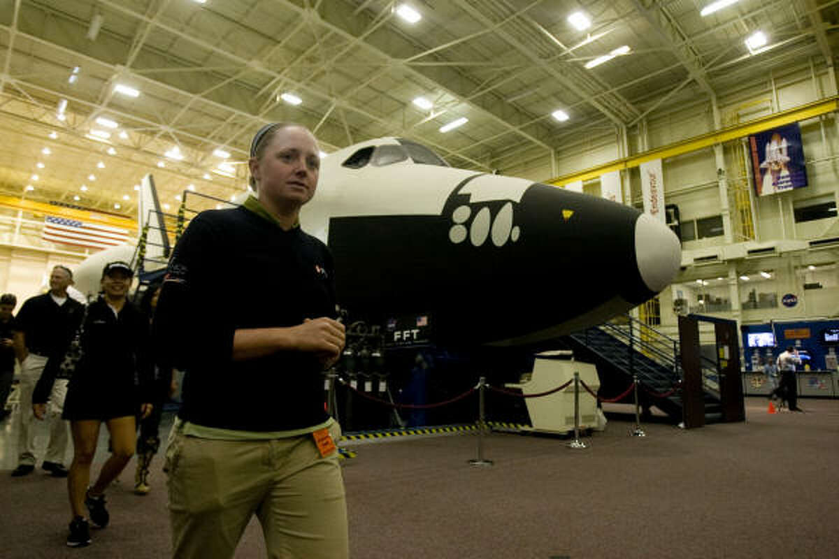 Stacy Lewis walks past a replica Space Shuttle used for training at the Johnson Space Center.