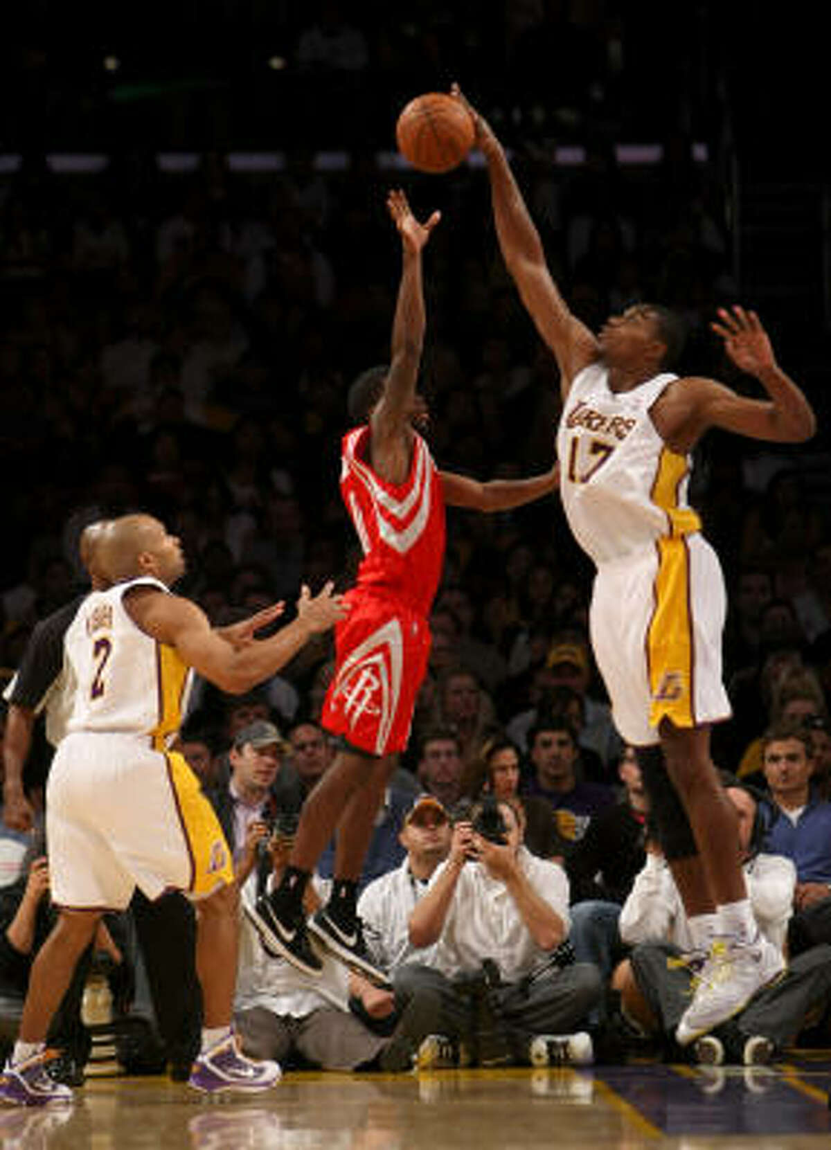 Lakers center Andrew Bynum, right, blocks a shot by Rockets guard Aaron Brooks, center.