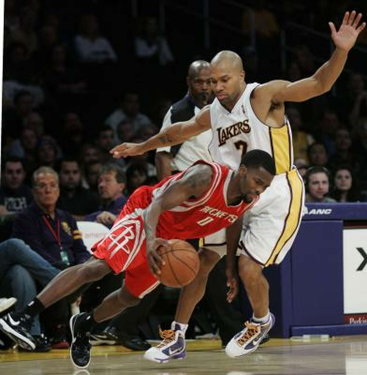 Rockets guard Aaron Brooks (0) drives around Lakers guard Derek Fisher during the second half.