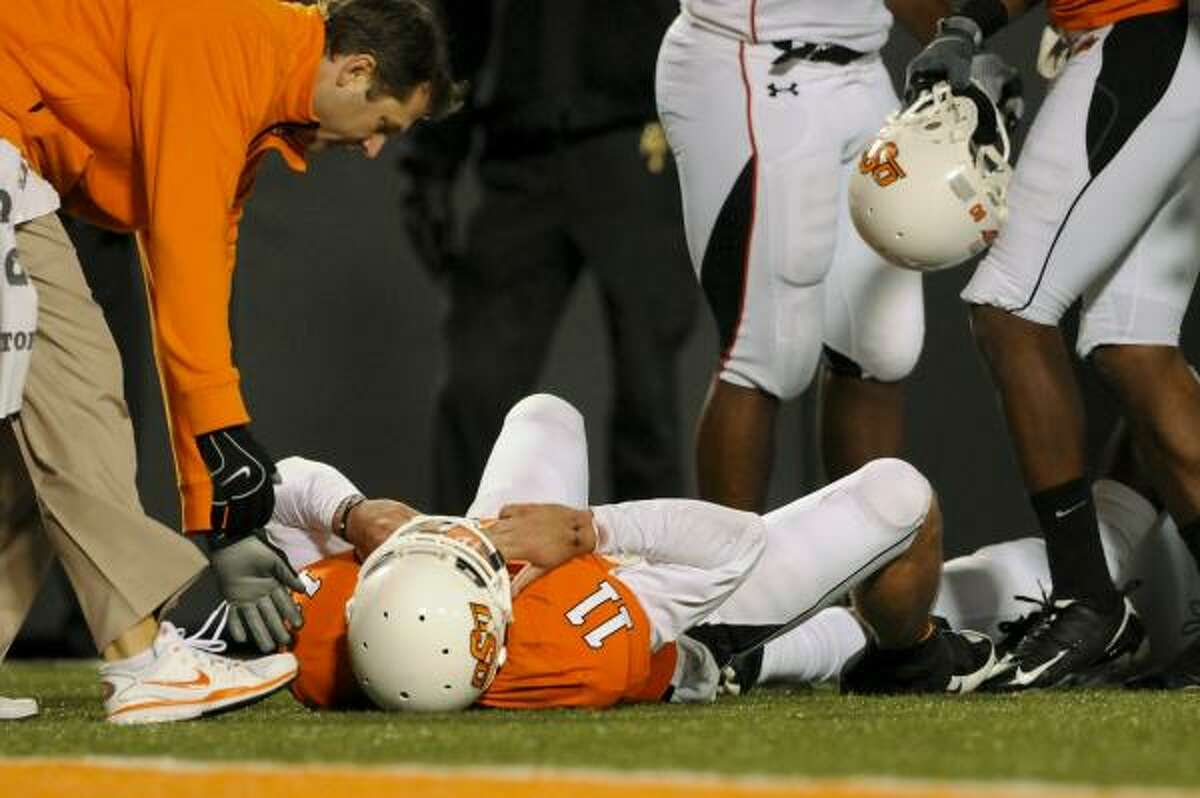 Oklahoma State quarterback Zac Robinson lies on the ground following a collision with a Texas Tech defender while members of the medical staff offer assistance during the second half.