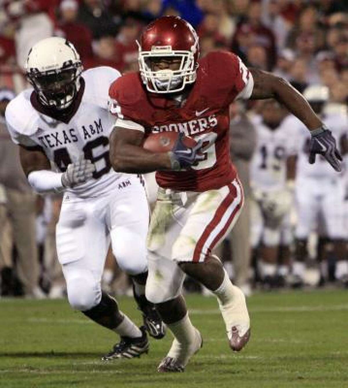 Oklahoma running back Chris Brown, right, rushes for six yards for a touchdown as Texas A&M defender Matt Featherston, left, trails the play in the second quarter of their matchup in Norman, Okla., Saturday.
