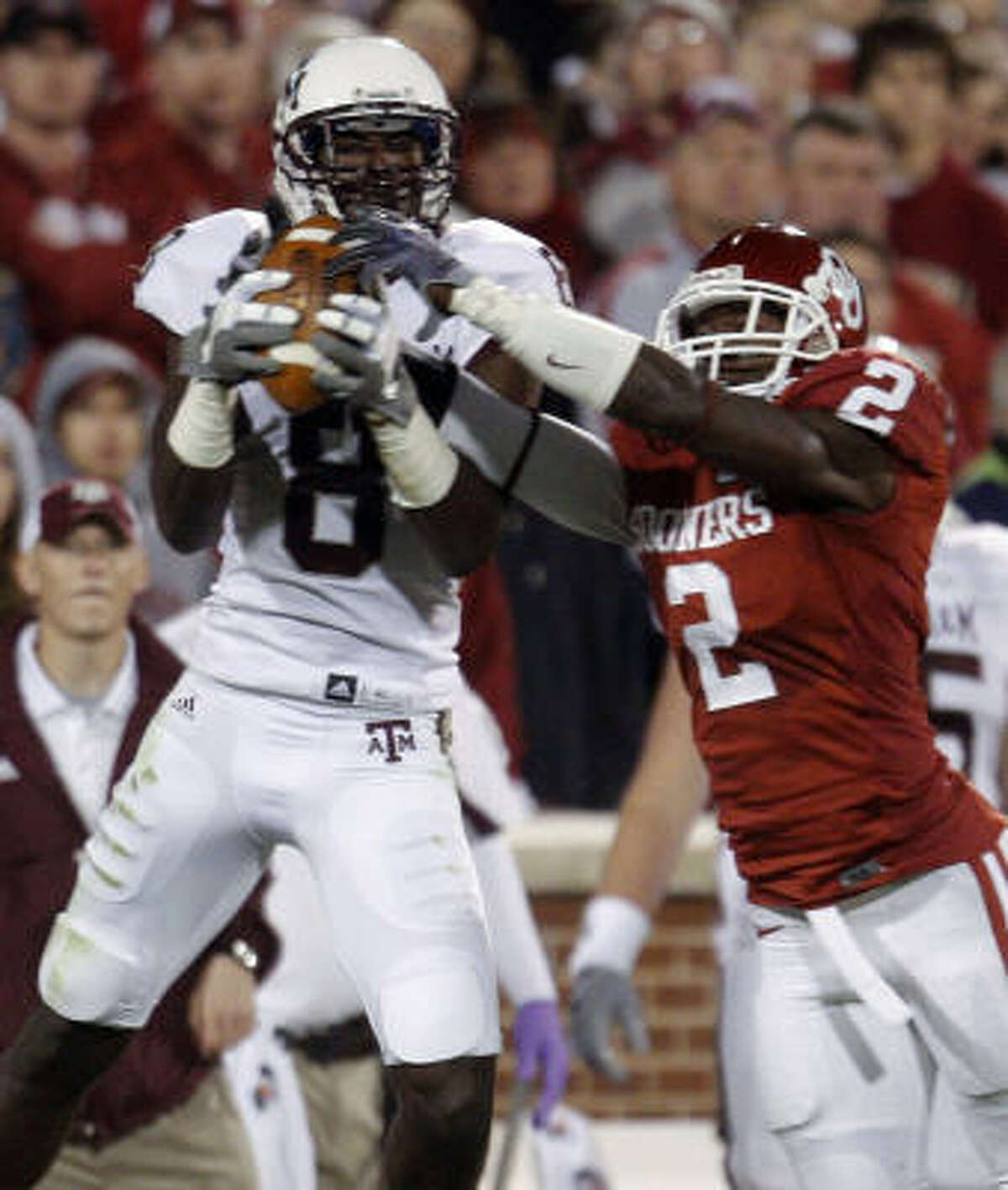 Texas A&M wide receiver Jeff Fuller, left, catches a pass in front of Oklahoma defender Brian Jackson, right, in the second quarter.