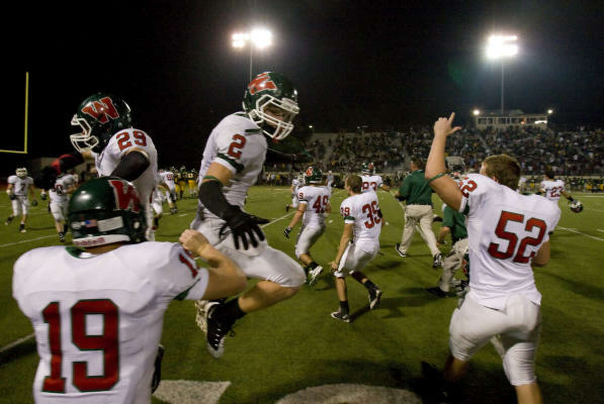 The Woodlands players storm the field in celebration after Klein Forest kicker Jacob Decker missed an extra point attempt in overtime.