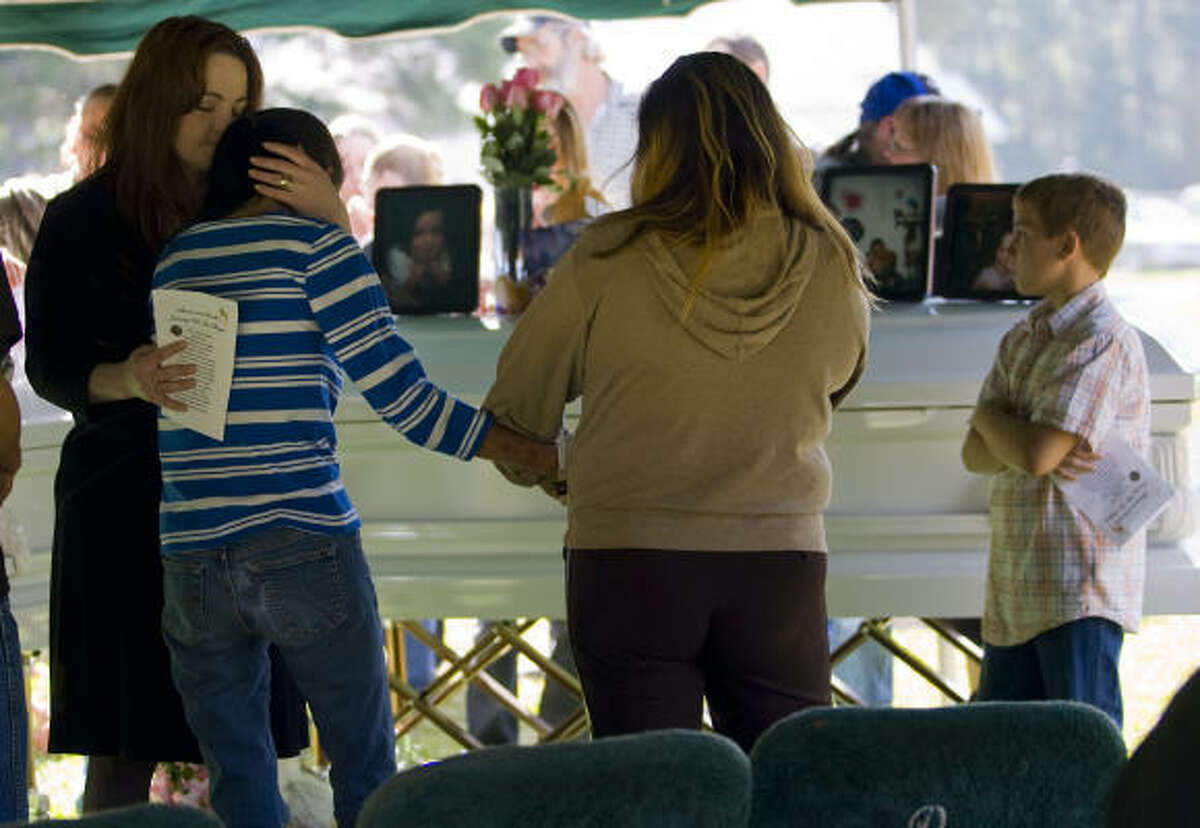 Sharon Clark is hugged by her sister, Nikki Nevarez and another family member during the funeral of Clark's daughter, Shara Torres, and her grand-daughter, Sarah Whitmire.