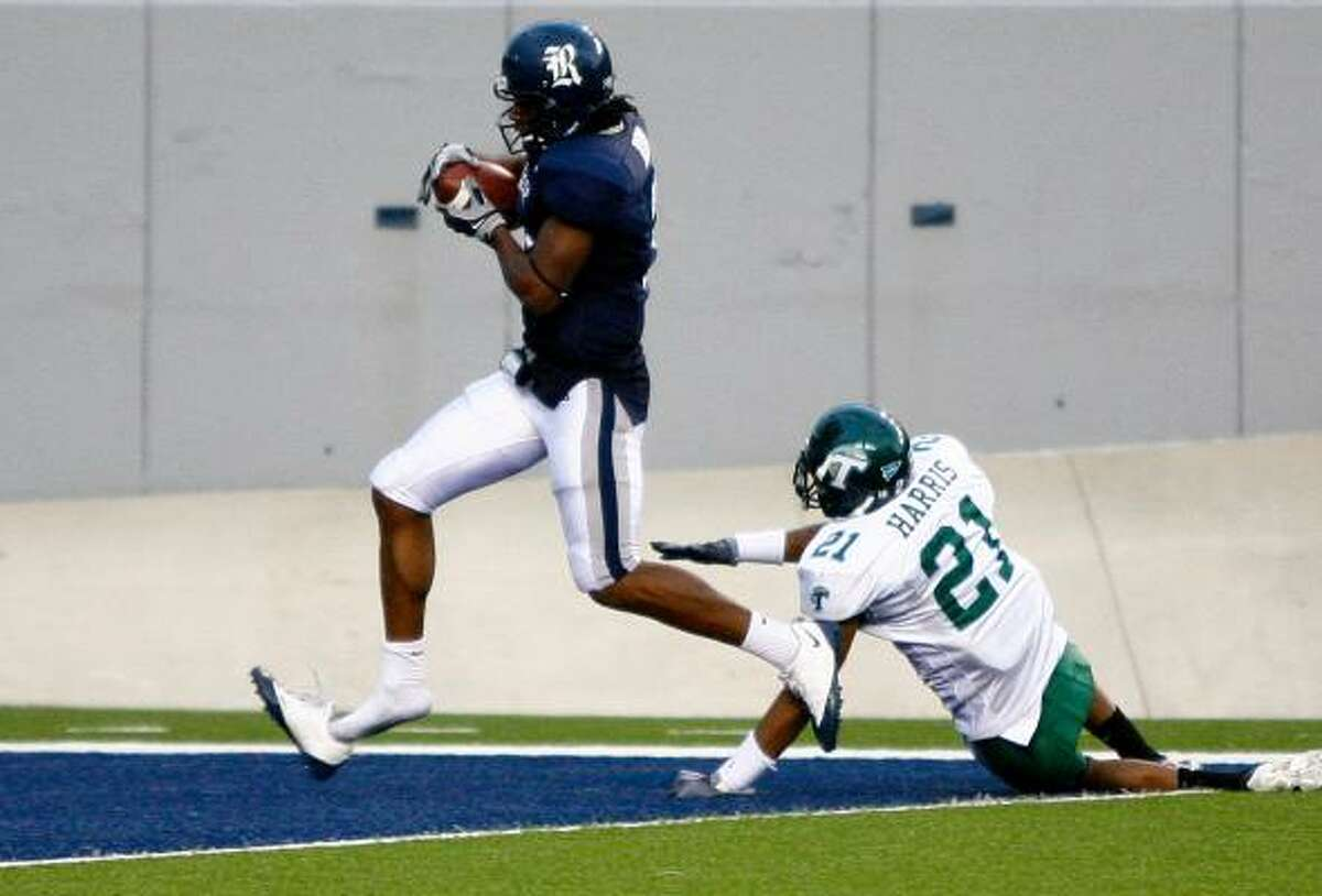 Rice quarterback Michael Poynter, left, loses his shoe as he scores the last touchdown of the game as Tulane cornerback Charles Harris (21) loses his footing in the fourth quarter.