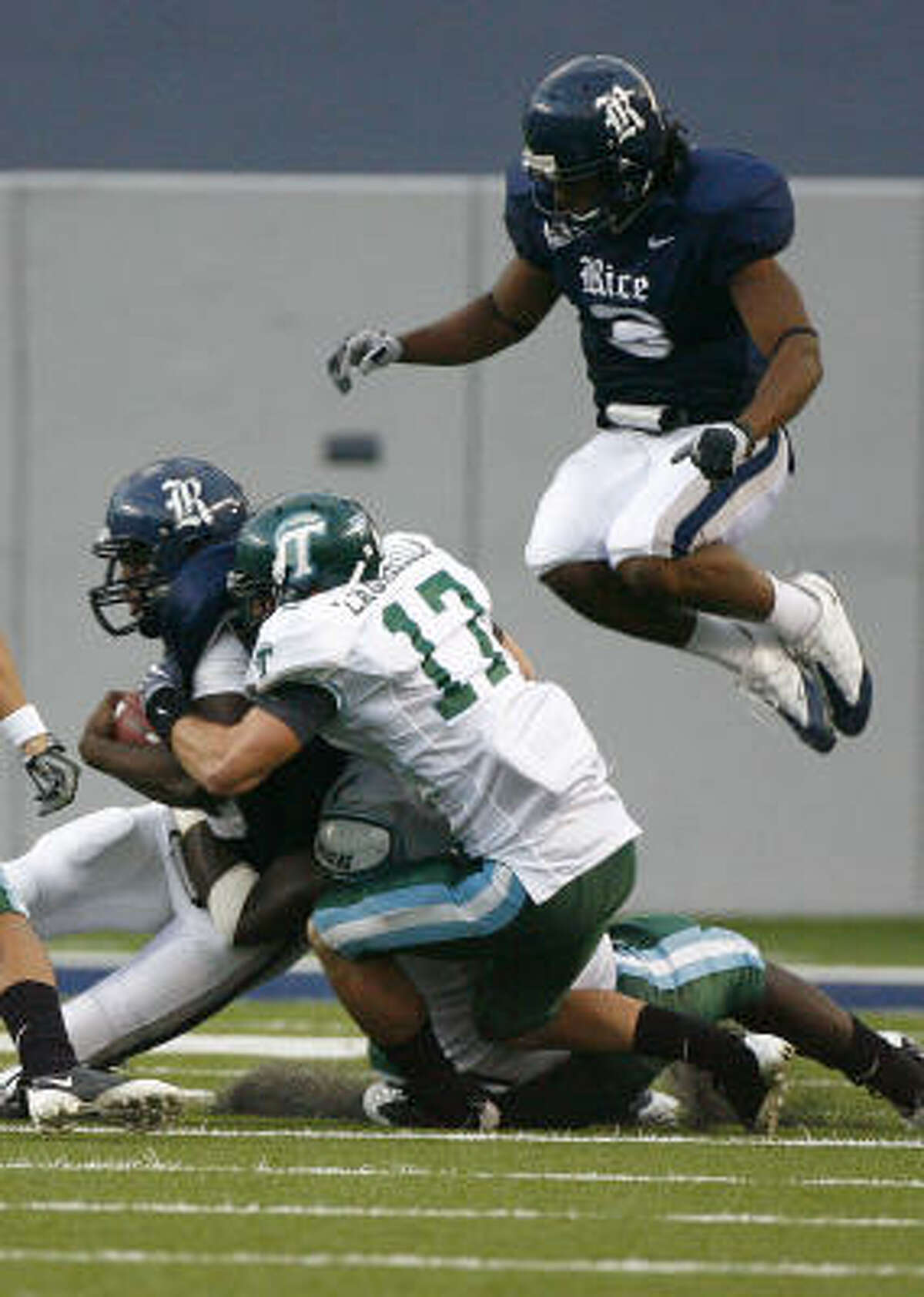 Rice running back Charles Ross (28) is tackled by Tulane cornerback Phillip Davis (13) in the fourth quarter.