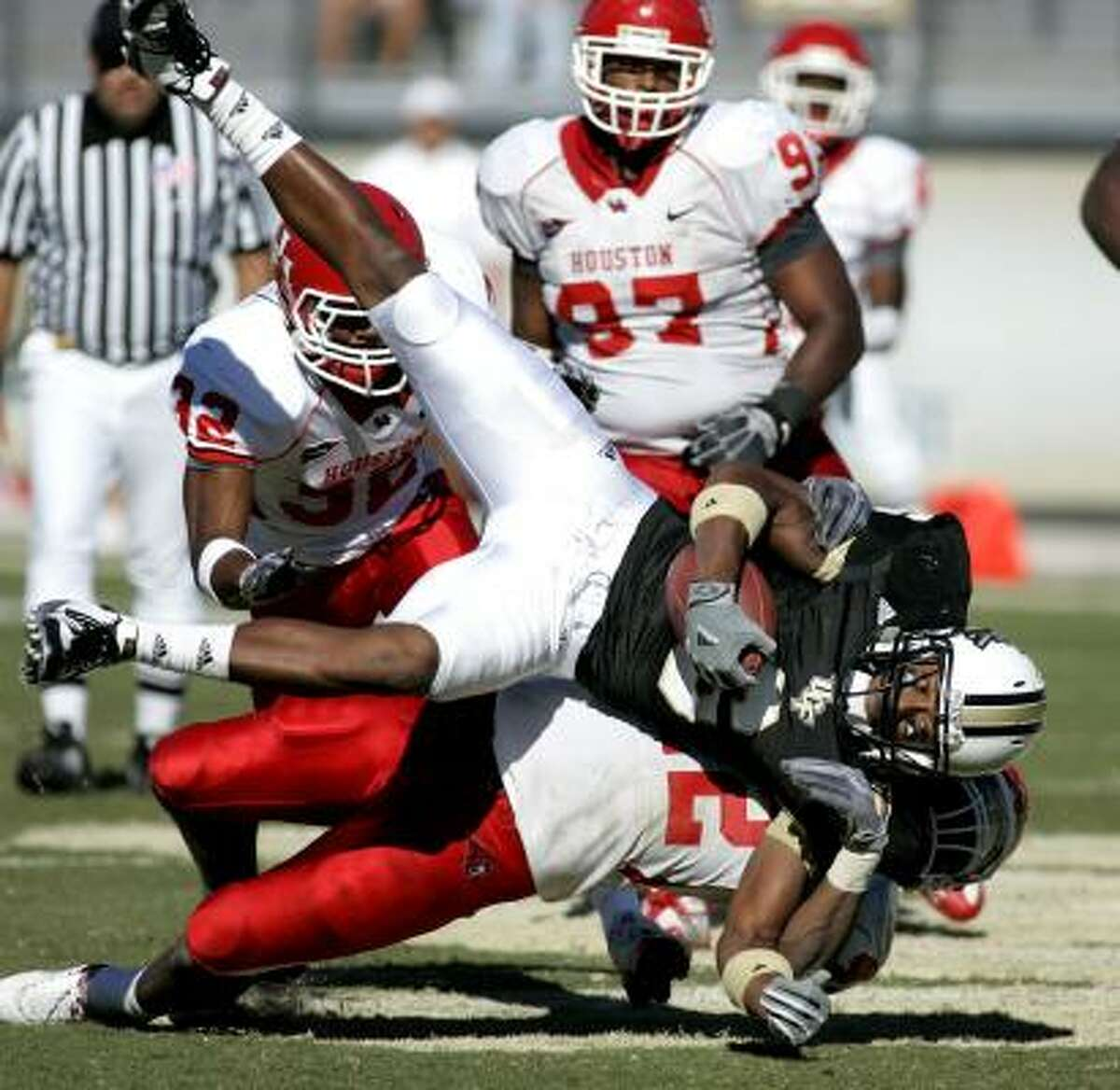Central Florida wide receiver Brian Watters is slammed to the ground by UH linebacker Phillip Steward (42).
