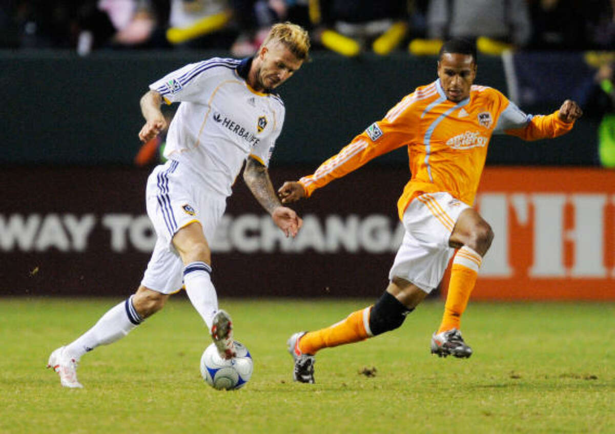 Los Angeles' David Beckham shoots a pass with the back of his heel against past Dynamo's Ricardo Clark in the first half.