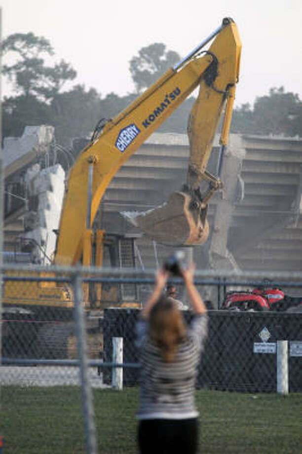 Michelle Cole of Humble ISD geta a photo of the demolition. Photo: Jerry Baker, For The Chronicle