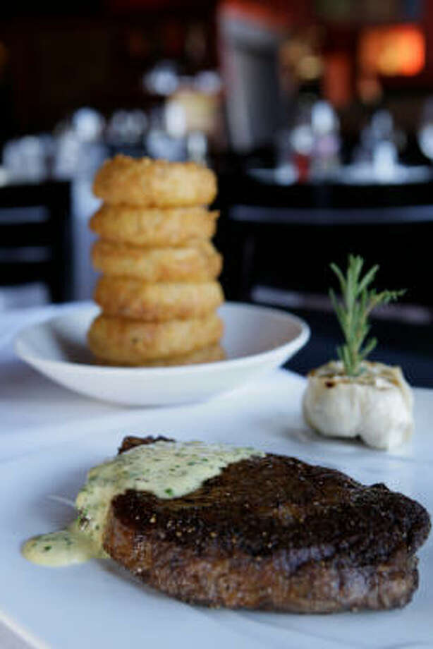 Tesar's Grass-fed ribeye with bearnaise sauce and a whole half-bulb of roasted garlic and onion rings. 1701 Lake Robbins Drive, The Woodlands. Read more about Tesar's. Photo: Melissa Phillip, Houston Chronicle