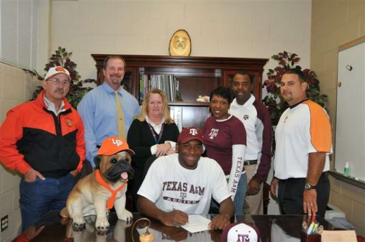 La Porte outfielder Kendrick Perkins (center) signs to play baseball with Texas A&M. Perkins, who is also a standout running back for the Bulldogs, is surrounded by his family and coaches.