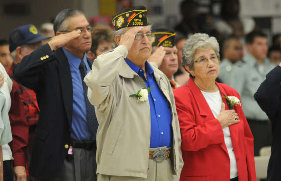Gene Morones, left, an Air Force veteran and a member of the Humble High School Class of 1971, and his wife, Mary, show their respect during the playing of the National Anthem at the Veteran's Day program at Humble High School. Photo: Jerry Baker, For The Chronicle