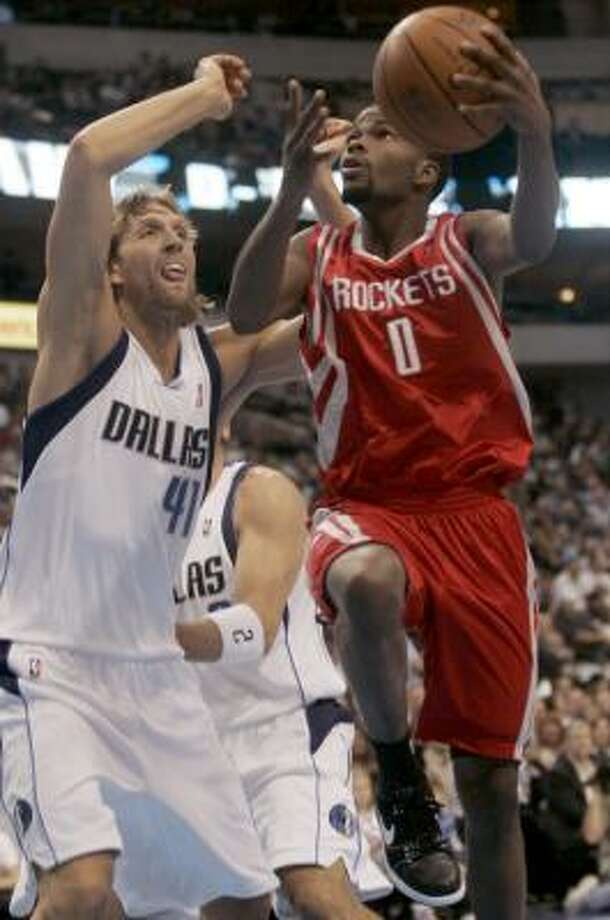 Rockets guard Aaron Brooks goes for a shot against Mavericks forward Dirk Nowitzki in the first quarter. Photo: Mike Fuentes, AP