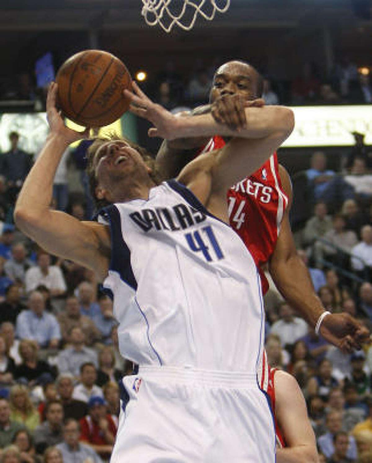 The Rockets' Carl Landry fouls Mavericks Dirk Nowitzki under the basket in the first quarter.