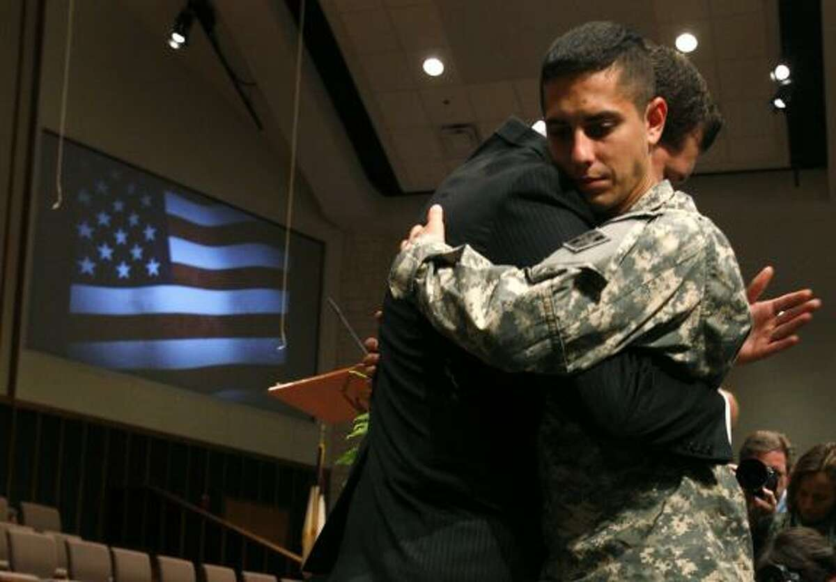 Rick Artus, pastor of Christian Life Church, left, embraces Pfc. Cameron Parrott after a prayer service at First Baptist Church in Killeen.