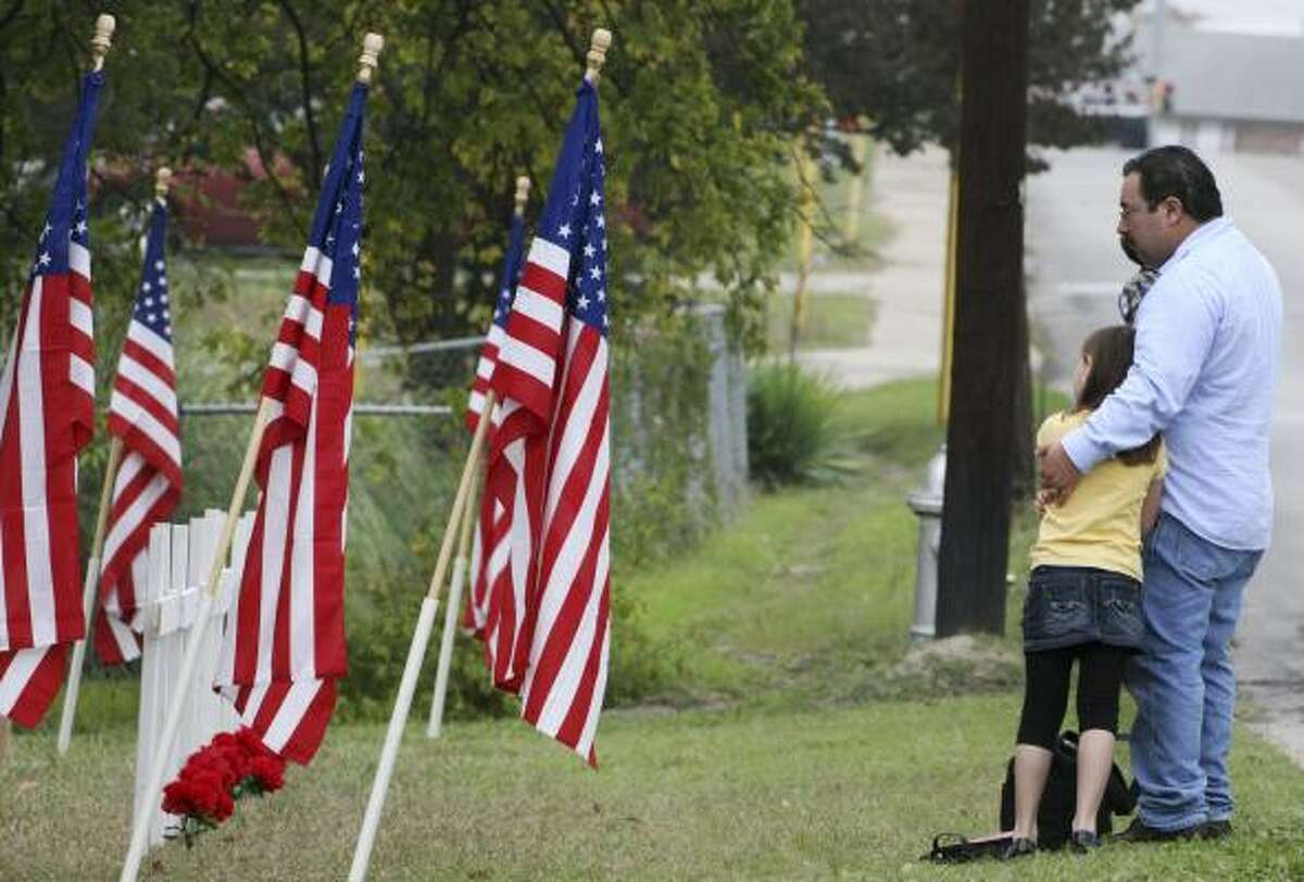 David Smith and his stepdaughter Hannah Shoopman visit a memorial to the Fort Hood victims in Killeen.
