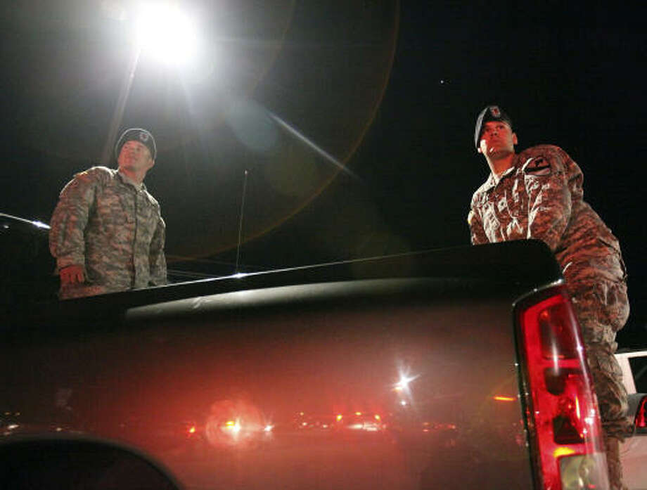 U.S. Army Specialists David Straub (left) and Ryan Howard wait to be let onto Fort Hood Army Base at the main gate in Fort Hood, Tx. Photo: EDWARD A. ORNELAS, SAN ANTONIO EXPRESS-NEWS