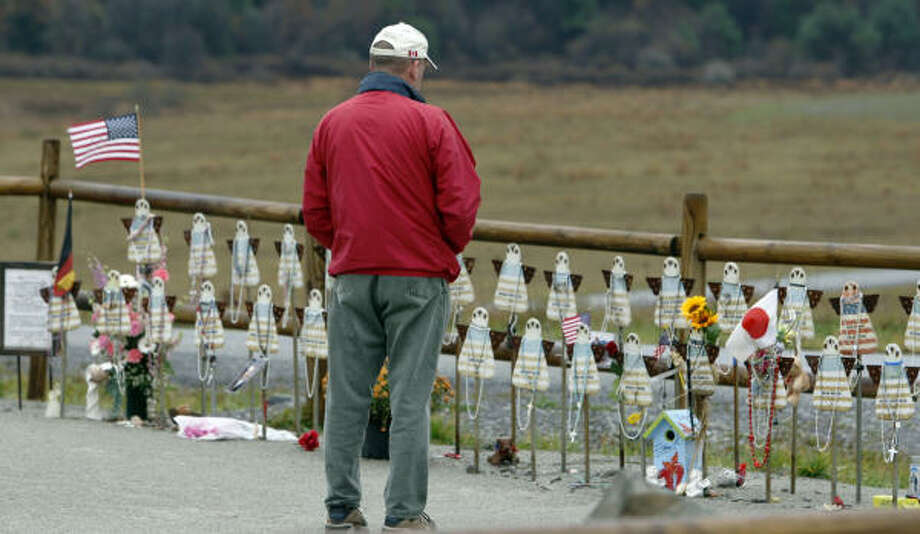 In this photo made on Oct. 28, 2009,  a visitor looks over markers for each of the victims at the temporary memorial near where Flight 93 crashed,   40 people perished there in the terrorist attack of Sept. 11, 2009  in Shanksville, Pa.. Photo: Keith Srakocic, AP