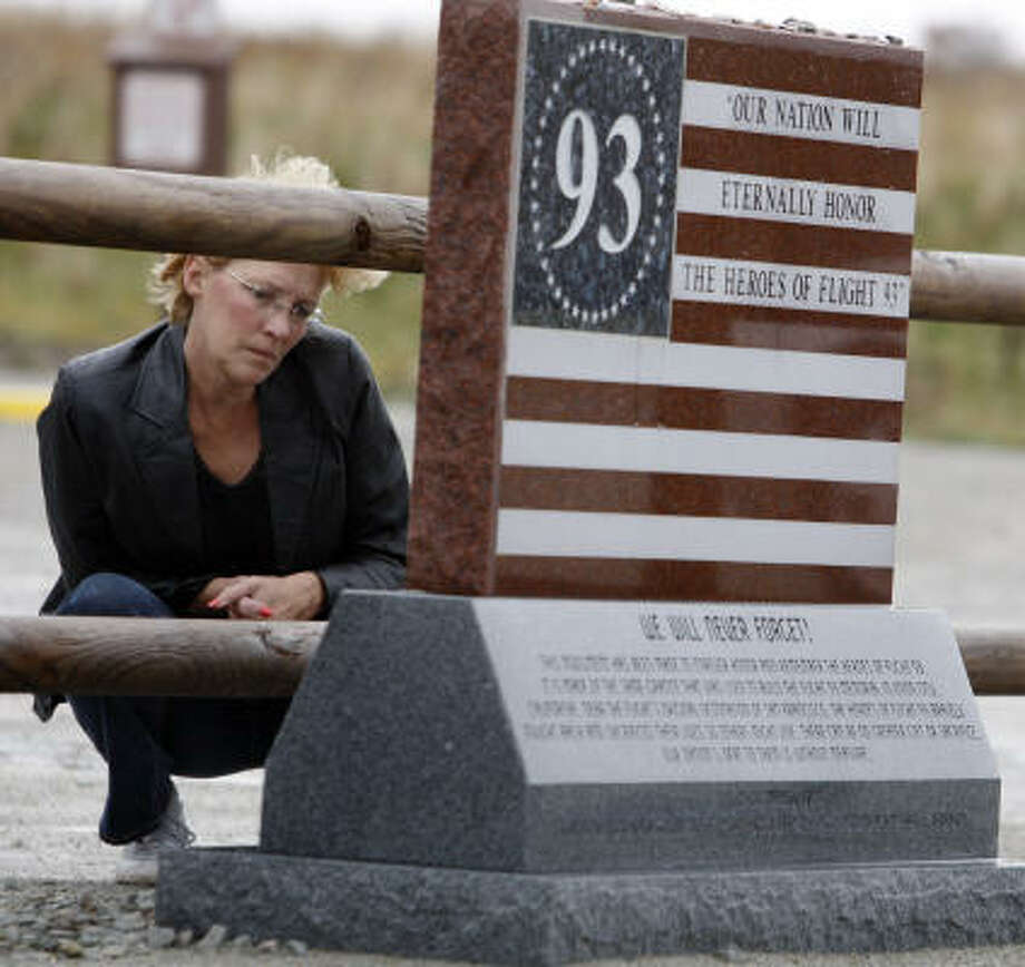"In this photo made on Oct. 28, 2009, Jan Edwards from Lebanon, Ohio, stoops to read the inscription on one of the markers at the temporary memorial for those that died in the Flight 93 crash in the  Sept. 11, 2001 attacks in Shanksville, Pa.. Small wooden signs with the words ""Flight 93"" point the way to the crash scene's temporary memorial. When the permanent memorial is completed, a 93-foot tall tower containing 40 wind chimes will mark the entrance. What victims' family members hope won't change, though, is the spirit of the people in Somerset County. Photo: Keith Srakocic, AP"