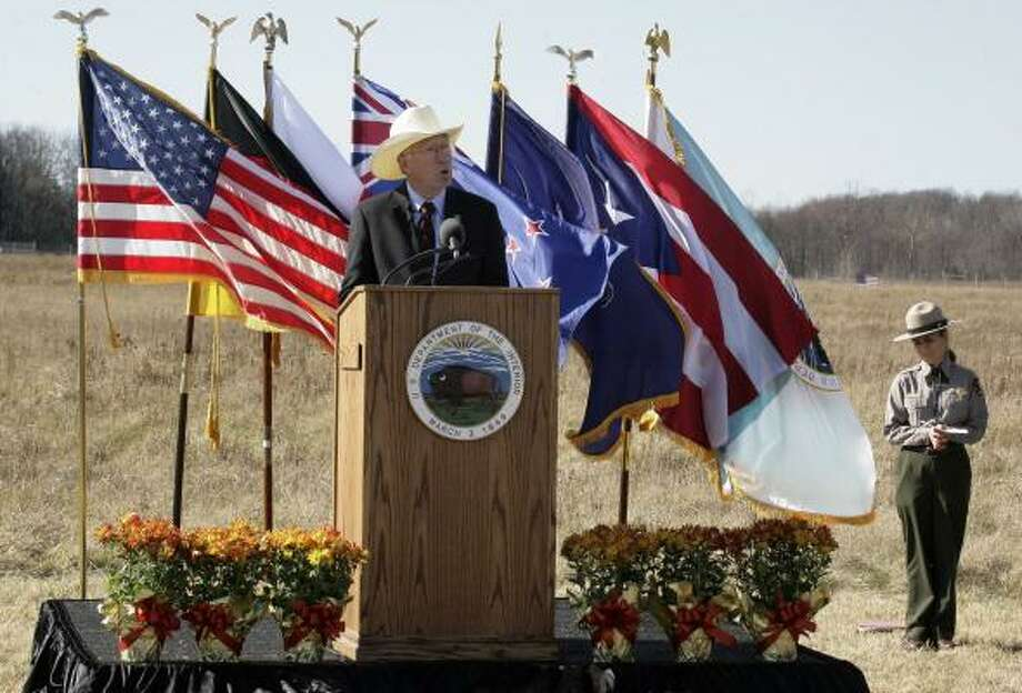 Secretary of the Interior Ken Salazar, left, makes remarks during the groundbreaking ceremony for the Flight 93 National Memorial Saturday, Nov. 7, 2009 in Shanksville, Pa. The flag in the field , right rear, marks the crash site of United Flight 93 on Sept. 11, 2001. Plans are to dedicate the new memorial on Sept. 11, 2011. Photo: Gene J. Puskar, AP