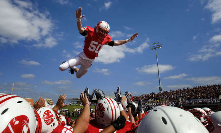 Katy linebacker Ben Bills leaps into his teammates' arms before the game at Rhodes Stadium. Photo: Smiley N. Pool, Houston Chronicle