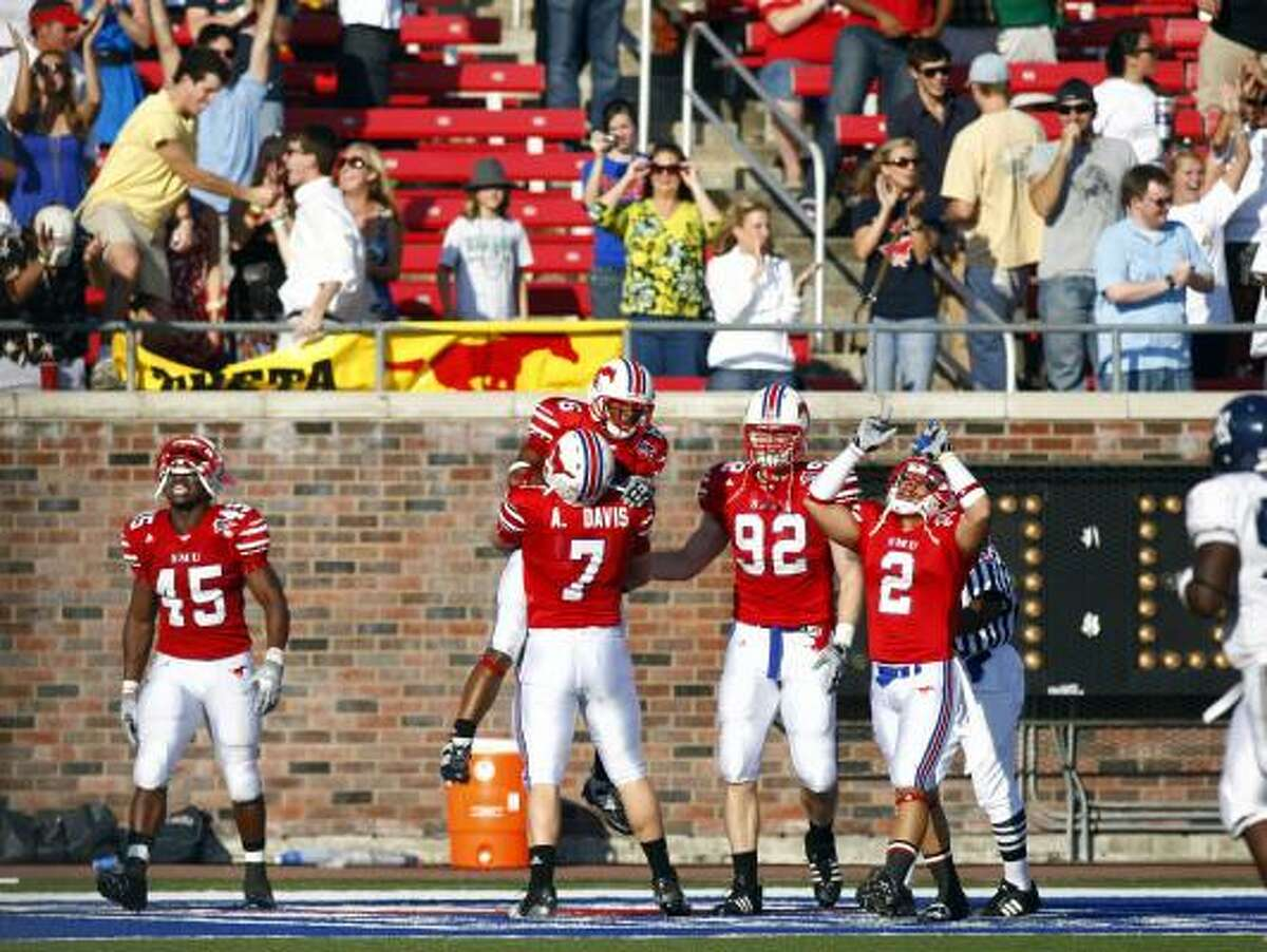 SMU's Bryan McCann celebrates with teammate Aaron Davis (7) and other teammates, including Youri Yenga (45), Margus Hunt (92) and Sterling Moore (2) after McCann returned a blocked field goal attempt for a toucdown during second quarter.