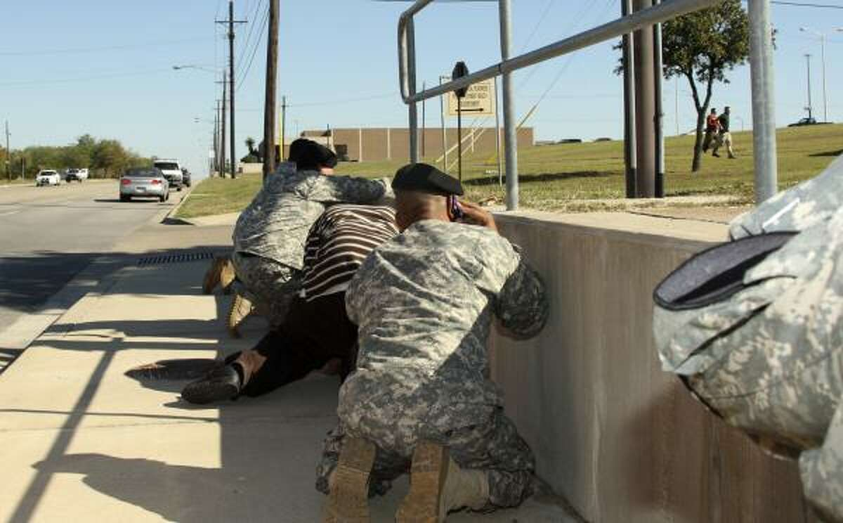 Bystanders crouch for cover as shots ring out from Fort Hood's Soldier Readiness Processing Center.