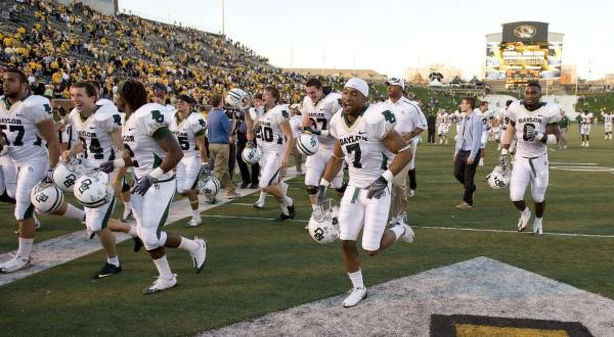 The Baylor team celebrate as it runs off the field after the victory.