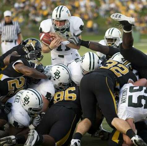 Baylor quarterback Nick Florence, top, tries to maintain control of the ball as he tries to score during the fourth quarter. Photo: L.G. Patterson, Associated Press