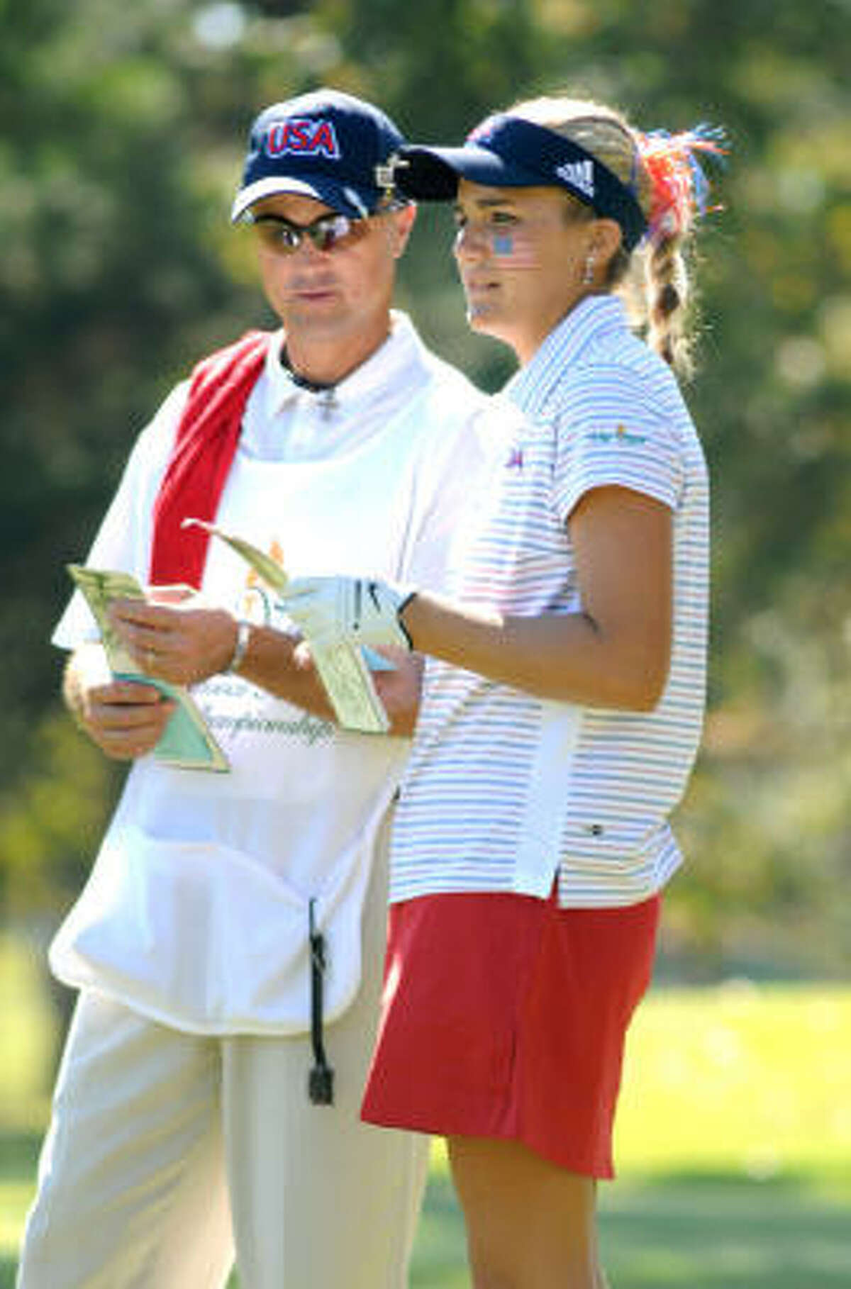 Alexis Thompson, 14, right, of Coral Springs, Fla., with her caddy, Randy Lance, of The Woodlands, checks the yardage on the par-4 No. 5 hole.