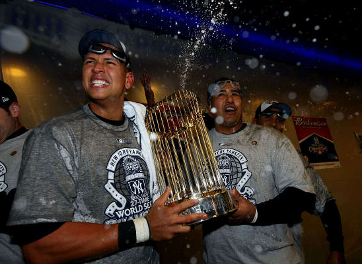 Yankees third baseman Alex Rodriguez and Jose Molina celebrate with the trophy in the locker room after their 7-3 win against the Philadelphia Phillies in Game 6 of the 2009 World Series.