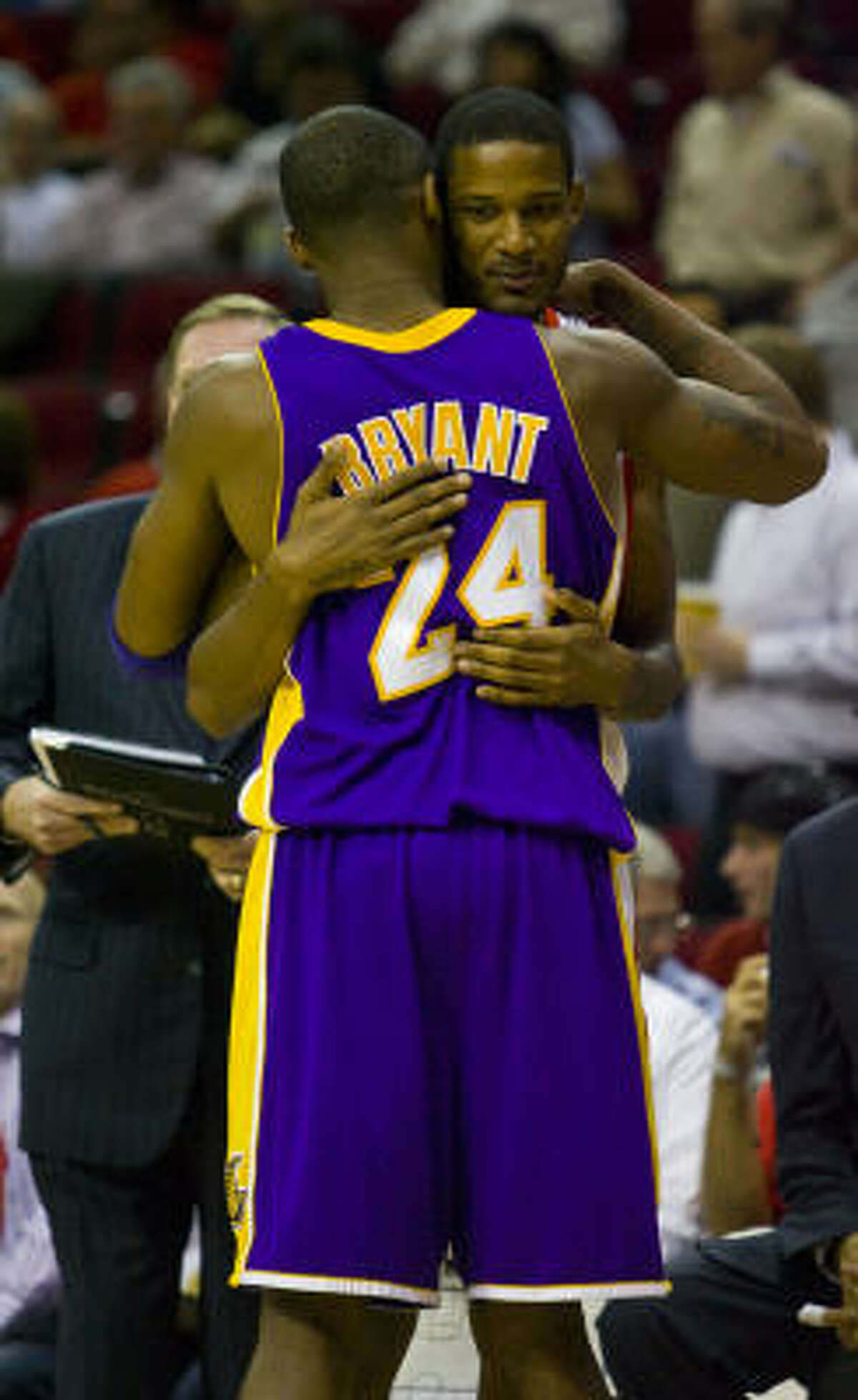 Rockets guard Trevor Ariza gets a hug from the Lakers' Kobe Bryant before the start of the game.