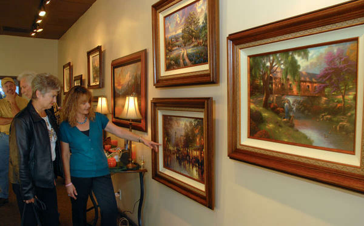 ART GALLERY: Sharon Roe, of Conroe, looks at a painting Gallery off the Square owner Cathy Cook is showing her during the art gallery's opening gala celebration in downtown Conroe. Two new art galleries have opened on Main Street in downtown Conroe, with more planned in the future.