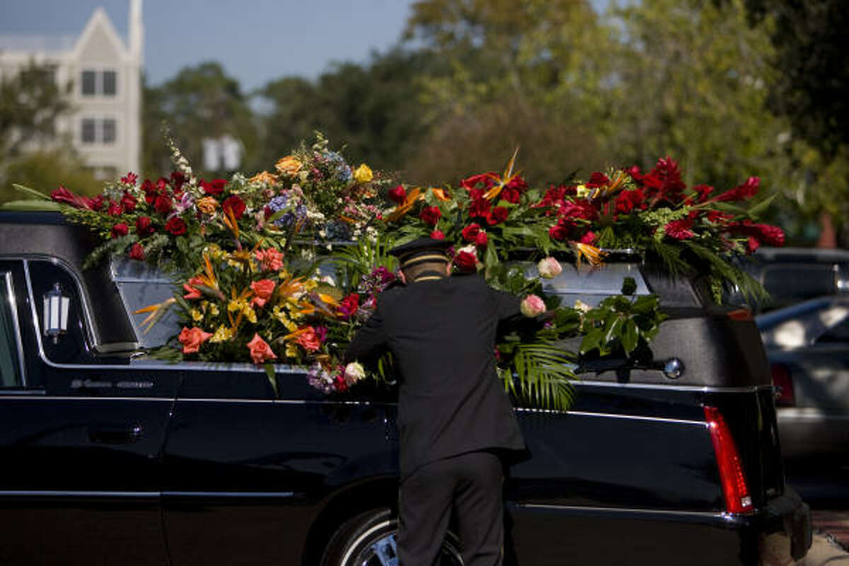 George Fernandez with George H. Lewis & Sons Funeral Home puts flowers on a hearse that will escort the casket of prominent attorney and philanthropist John O'Quinn.
