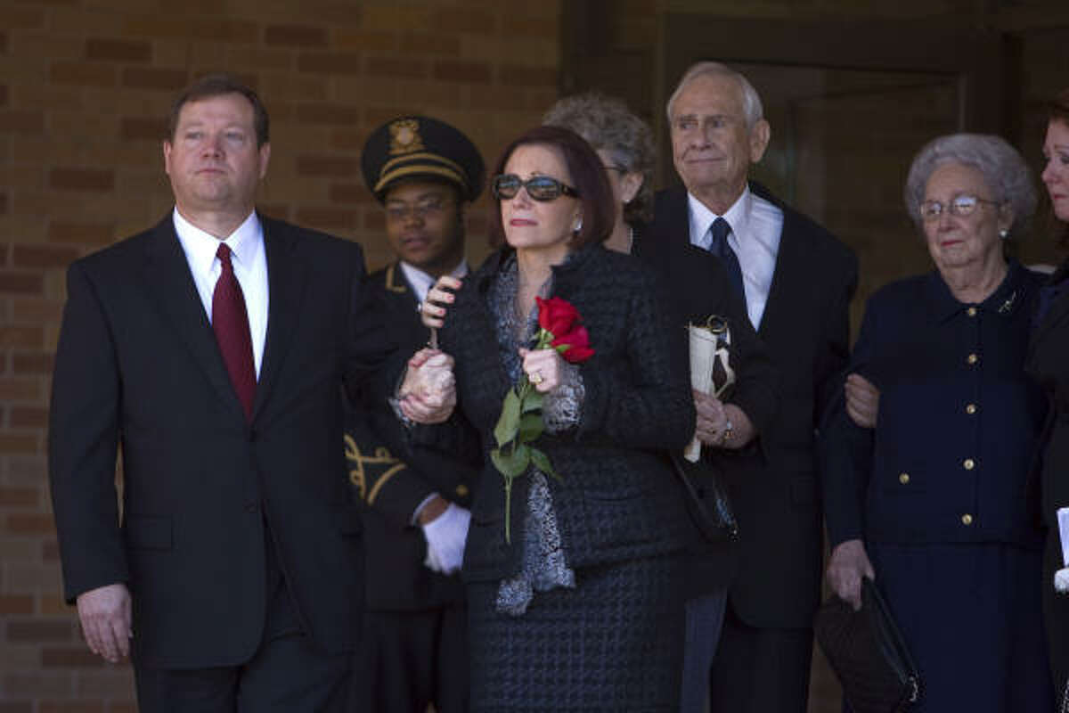 Darla Lexington, center, the companion of John O'Quinn, walks out of Second Baptist Church.