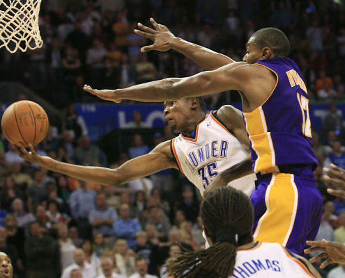 Oklahoma City Thunder forward Kevin Durant, left, goes up for a shot in front of Los Angeles Lakers center Andrew Bynum, right, in overtime in Oklahoma City.