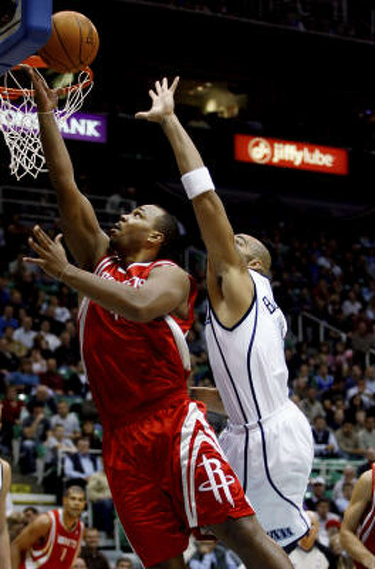 Chuck Hayes puts in a layup as Jazz forward Carlos Boozer is unable to stop him. Hayes shot 6-for-8 from the floor for 12 points, making him one of eight Rockets in double-figures.